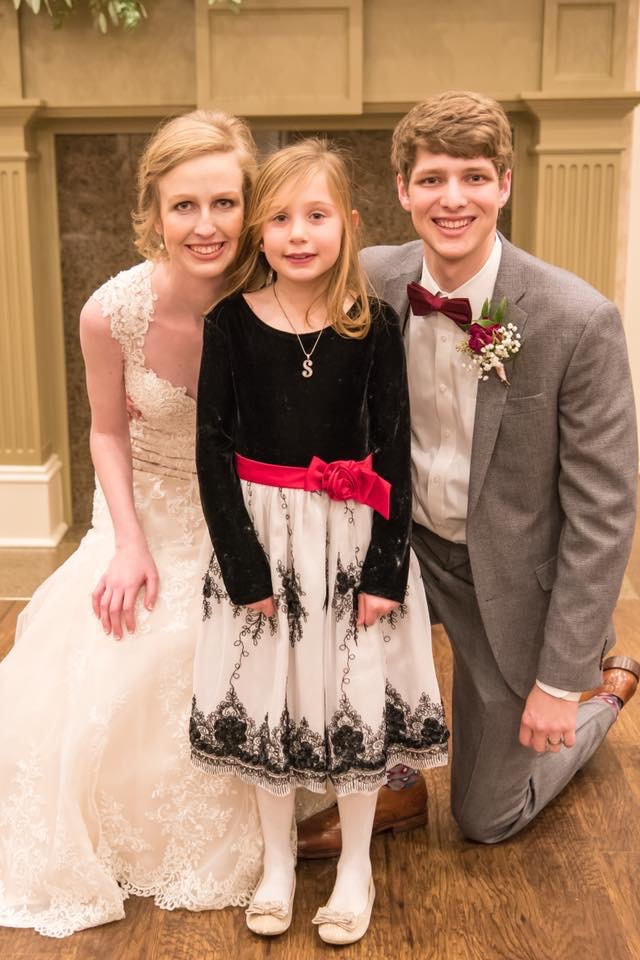 Baron and her spouse, Oakley Baron '16, share a moment with their Kindergarten buddy at their wedding.